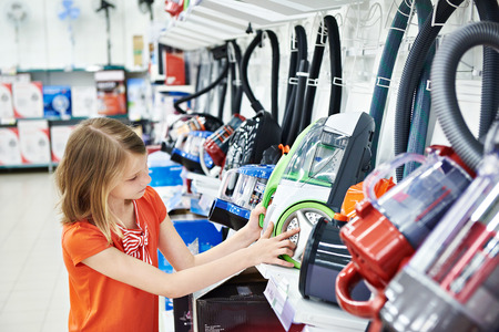 10's: Little girl shopping for electric vacuum cleaner, smiling Stock Photo