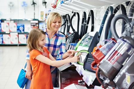 chicas comprando: Madre e hija de compras para aspiradora eléctrica, sonriendo Foto de archivo