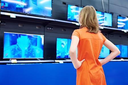 Teenager girl looks at LCD TVs in supermarket Фото со стока - 43691532