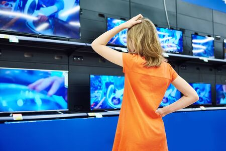 sale shop: Teenager girl looks at LCD TVs in supermarket