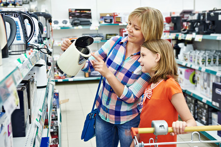 Mother and daughter shopping for electric kettle, smiling Banco de Imagens