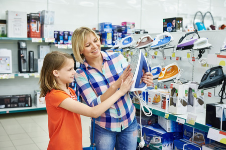 appliances: Mother and daughter shopping for electric iron, smiling