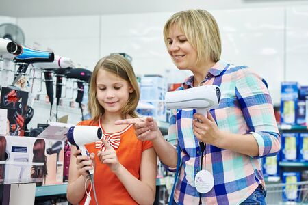 hairdryer: Mother and daughter chooses a hairdryer in the store Stock Photo