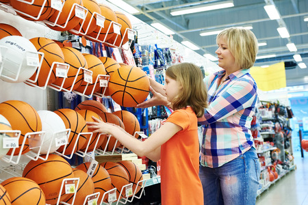 Mother and daughter shopping basketball ball in sport shop Banco de Imagens