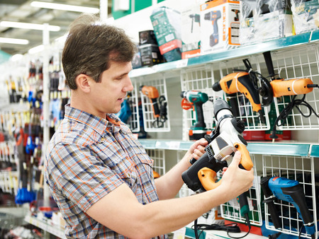 Man shopping for perforator in hardware store close-up Archivio Fotografico