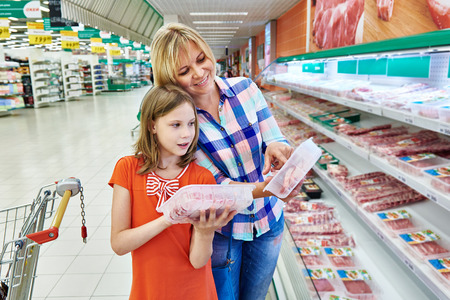 Мать и дочь выбирает мясо в супермаркете