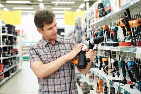 Человек по магазинам для перфоратора в хозяйственный магазин крупным планом