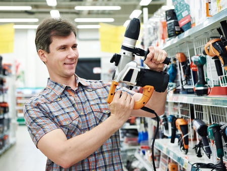 Man shopping for perforator in hardware store close-up Stockfoto