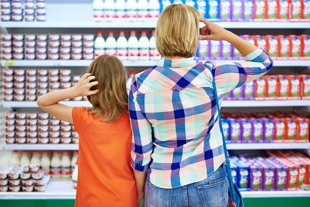Madre e hija la elección de productos lácteos en la tienda