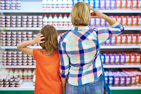 packaging: Mother and daughter choosing dairy products in shop