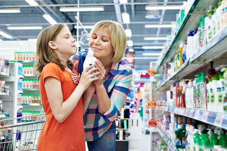 Mother and daughter sniff fragrance shampoo in supermarket