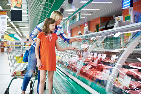 Mother and daughter chooses a meat in the supermarket Stock Photo - 43959022