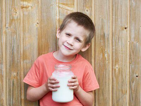 glass jar: Boy with glass jar of fresh milk near wood wall