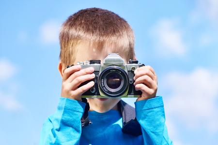 Little boy with retro SLR camera shooting on blue sky Фото со стока