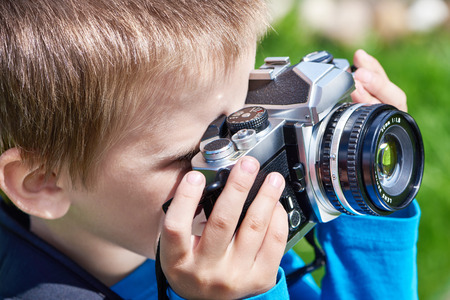 slr: Little boy with retro SLR camera shooting Stock Photo