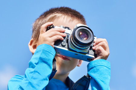 slr: Little boy with retro SLR camera shooting on blue sky Stock Photo
