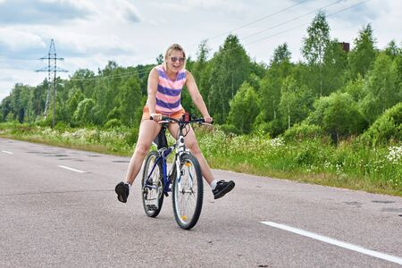Happy woman riding a Bicycle on the road in summer Sunny day Stock Photo