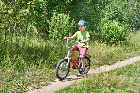 Little boy on a bike ride on a country road