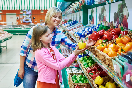 bell peppers: Mother and daughter chooses bell peppers in the supermarket Stock Photo