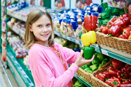 bell peppers: Girl with varicolored bell peppers in the supermarket
