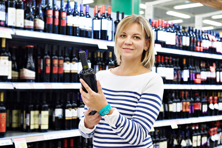 wine trade: Woman with bottle of wine in the store