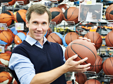 Man chooses ball for basketball in the sports shop