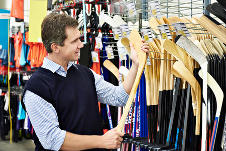 Man chooses hockey stick in the sports shop