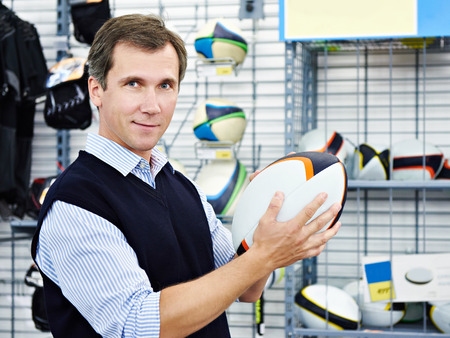 Man chooses ball for rugby in the sports shop