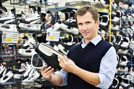 Man chooses hockey skates in the sports shop