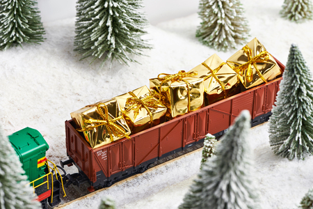 Holiday train carries gifts for Christmas on winter forest