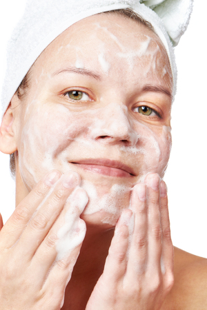 cleanse: Woman clears a face skin foam on white background Stock Photo