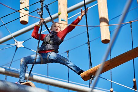 climbing cable: Brave girl is climbing to amusement park