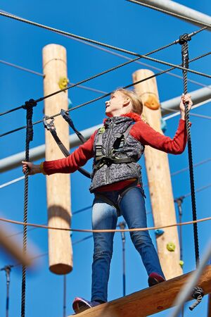 climbing cable: Girl athlete runs an obstacle course in climbing amusement park