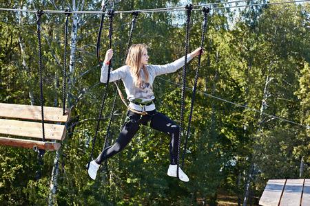 escalando: Chica atleta corre una carrera de obstáculos en la escalada parque de diversiones