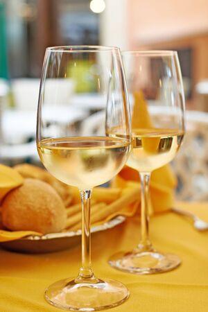 tela blanca: Vasos de vino blanco y una ensalada en el vector del café