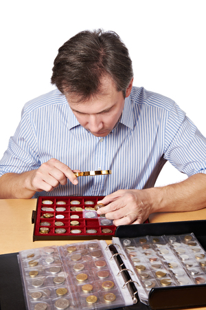 numismatist: Man numismatist examines with a magnifying glass  coin from his collection