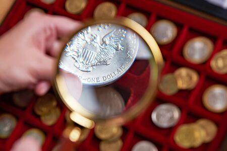 Американский доллар под увеличительным стеклом в руках нумизмата