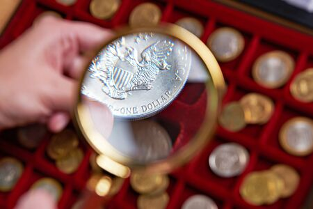 numismatist: American dollar under magnifying glass in hands of numismatist Stock Photo