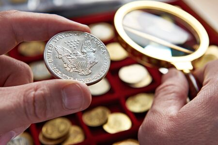 numismatics: American dollar in hands of numismatist and magnifying glass