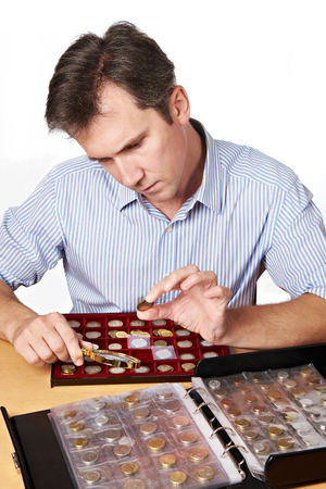 numismatist: Man numismatist examines coin from the collection isolated