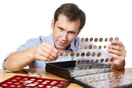 numismatist: Man numismatist examines his collection of coin  isolated