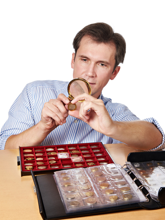 numismatist: Man numismatist examines with a magnifying glass coin from his collection isolated Stock Photo