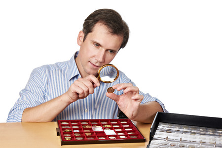 numismatics: Man numismatist examines with a magnifying glass coin from his collection isolated Stock Photo