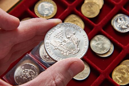 American dollar in hand of numismatist and magnifying glass