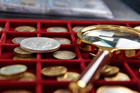 Американский серебряный доллар и увеличительное стекло на коробке с монетами