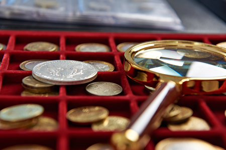 numismatic: American silver dollar and magnifying glass on box with coins Stock Photo