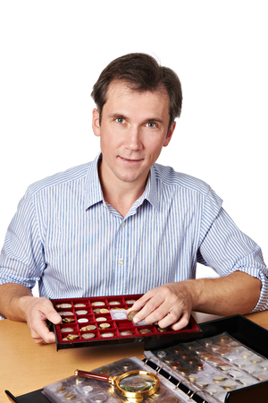 numismatist: Happy man with his collection numismatist coins isolated Stock Photo
