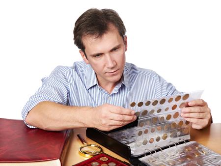 monete antiche: L'uomo numismatico esamina la sua collezione di moneta isolata Archivio Fotografico