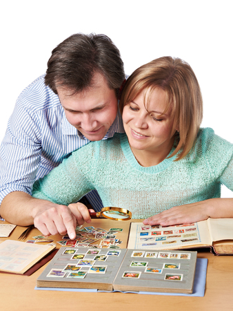 postage stamps: Man and woman watching a collection of postage stamps
