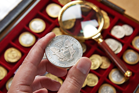 numismatist: American dollar in hands of numismatist and magnifying glass